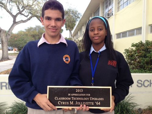 ACND Prep Daniel Briz and Darby Vilme hold Cyrus Jollivette Retirement Plaque